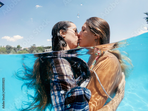 Two lesbian women having fun in swimming pool one summer afternoon Tableau sur Toile