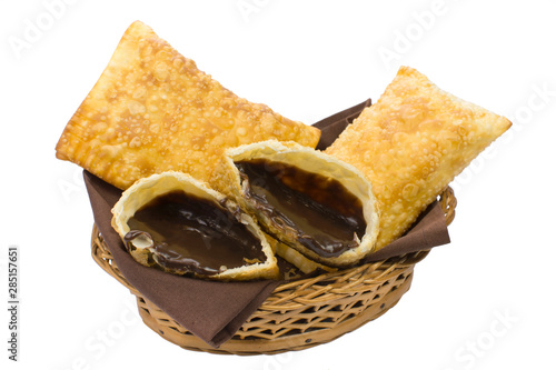 Fototapeta Tradional Brazilian fried pastry called pastel stuffed with chocolate Brazilian dessert brigadeiro with one open in a basket isolated in white background obraz