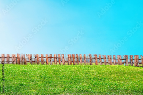 Photo Stands Turquoise landscape of green lawn and blue sky divided in half by fence
