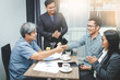 Asian business group sitting in the office meeting Two men join hands to make the event a success.