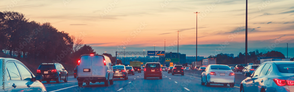 Fototapeta Night traffic. Cars on highway road at sunset evening in busy american city. Beautiful amazing urban view with red, yellow, blue sky. Sundown in downtown. Web header banner for website.