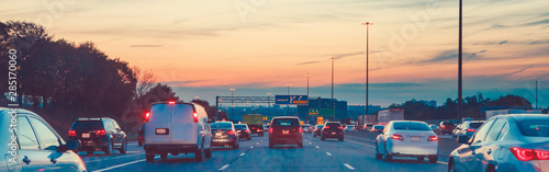 Photo sur Toile Autoroute nuit Night traffic. Cars on highway road at sunset evening in busy american city. Beautiful amazing urban view with red, yellow, blue sky. Sundown in downtown. Web header banner for website.