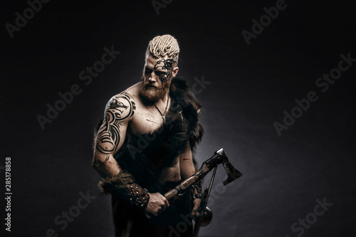 Foto Medieval warrior berserk Viking with tattoo on skin, red beard and braids in hair with axe and shield attacks enemy