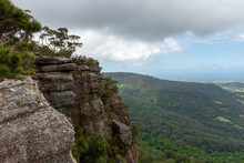 A Rocky And Grey Cliff Edge With Trees And Vegetation On Top, Overlooks The Dense Australia Forest on A Partially Cloudy Day At Drawing Room Rocks In NSW, Australia