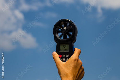 Photo Man measuring wind speed with Digital Anemometer.