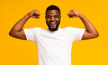 African American Man Smiling And Showing Biceps At Camera