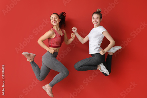 fototapeta na drzwi i meble Jumping sporty women on color background