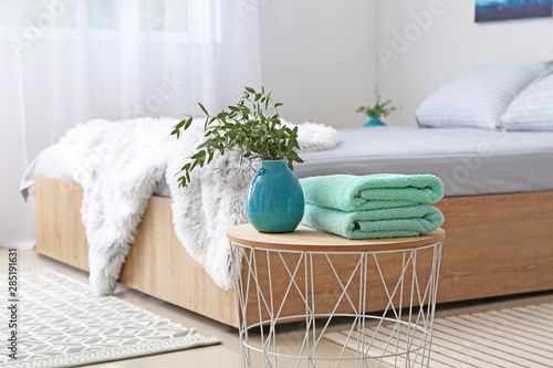 Valokuva  Stack of clean towels on table in bedroom