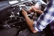 Close up of a man fixing broken car engine.