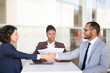 Two business partners closing deal, while legal expert explaining contract details. Multiethnic business man and women sitting at table, checking papers and shaking hands. Agreement concept