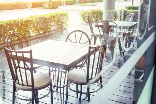 Stampa su Tela  Outside shop in sunny day with tables and chairs of cafe , restaurant in the morning time which nobody uses them