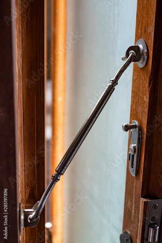 Aluminium Latch  is connected to ajar frosted Glass and wooden door frame, Close Wallpaper Mural