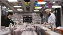 Trucking Shot Of Multiethnic Customers Browsing Through Records In Music Shop, And Stylish Caucasian Woman In Thirties, Wearing Bowler Hat And Glasses, Choosing Two Vinyls In White Covers And Leaving