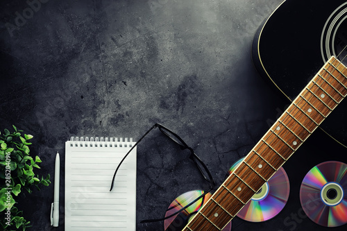 Guitar and accessories on a stone background. Desk musician, headphones, microphone. - 285204096