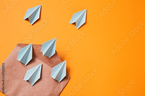 Fototapeta Concept for sending e-mails and e-commerce business. Email marketing. Paper planes flying out of the envelope obraz