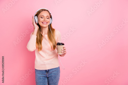 Photo of beautiful lady eyes closed listen favorite playlist earflaps takeout paper coffee wear pastel pullover isolated pink background - 285210064