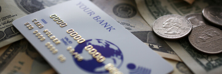 Credit card lying at big amount of US currency closeup