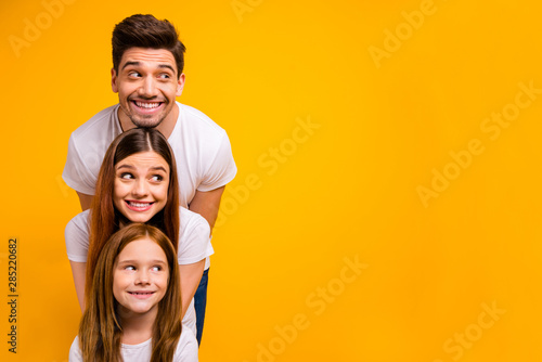 Obraz Portrait of three nice attractive charming lovely cute cheerful cheery person in order of hierarchy duty looking aside copy space isolated over bright vivid shine yellow background - fototapety do salonu