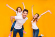 Leinwandbild Motiv Portrait of three nice attractive charming cute lovely stylish trendy cheerful cheery carefree playful glad person having fun time dancing isolated over bright vivid shine yellow background