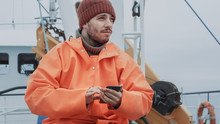 Casualy Dressed Fisherman Using Mobile Phone While Traveling On Ship.