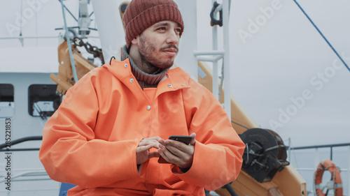 Fotografia, Obraz Casualy Dressed Fisherman Using Mobile Phone while Traveling on Ship