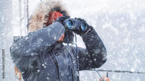 Fototapeta Polar Scientist and Adventurer in Warm Jacket Standing on Ship and Looking through Binoculars