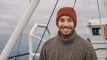 Portrait Of Casualy Dressed Smiling Fisherman On Commercial Fishing Boat.