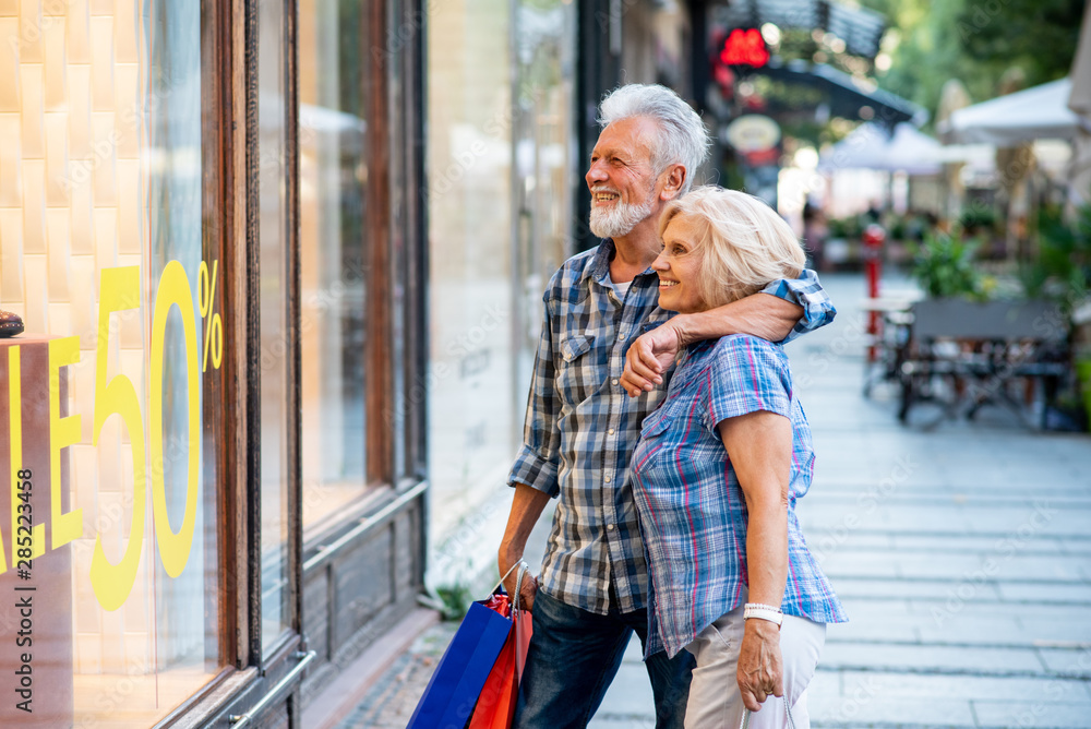 Fototapeta Happy senior couple in shopping looking at window