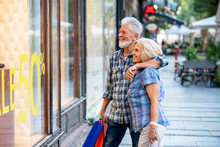 Happy Senior Couple In Shopping Looking At Window