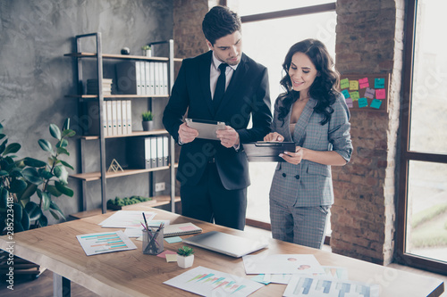 Obraz Photo of two business people partners share startup details standing workstation office dressed formal wear suits - fototapety do salonu