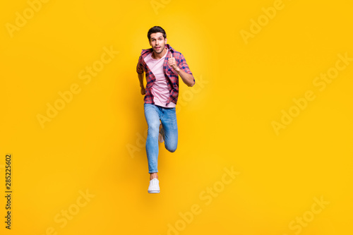 Fototapety, obrazy: Full length body size photo of serious running man looking at camera moving towards it while isolated with yellow background