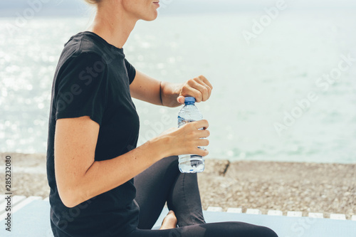 Photo A woman during a break in an outdoor training session on the seashore opens a bottle of water to quench her thirst