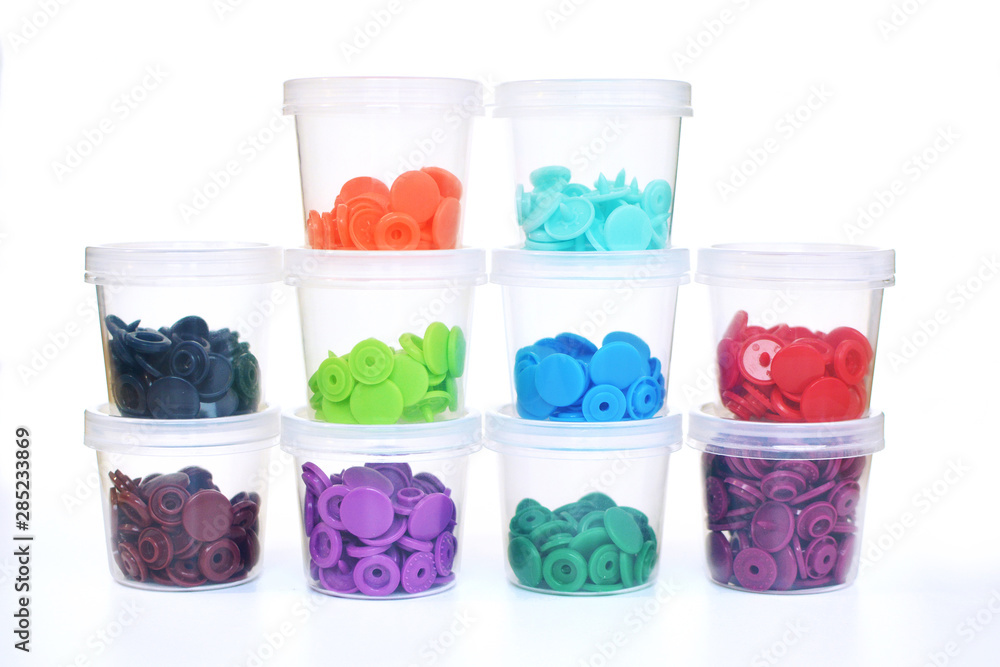 Fototapety, obrazy: Staples of colorful plastic snap fastener buttons in transparent containers on white background