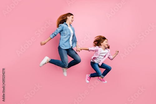 Foxy small lady and her mom jumping high rushing toy shop wear casual jeans outfit isolated pink background - 285234278