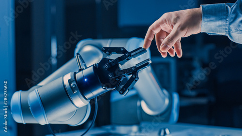 Fotografie, Obraz  Futuristic Robot Arm Touches Human Hand in Humanity and Artificial Intelligence Unifying Gesture