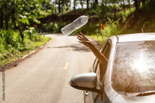 Fotografía Male driver throwing away plastic bottle from car window on the road,man's hand