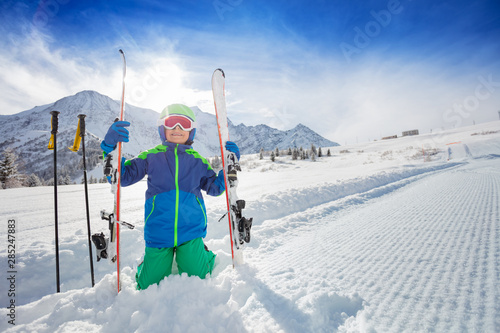 Fototapeta Portrait of a boy sit in snow with ski on slope