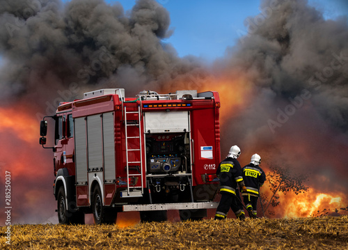 fire truck and firefighters during the fire extinguishing action Fototapet