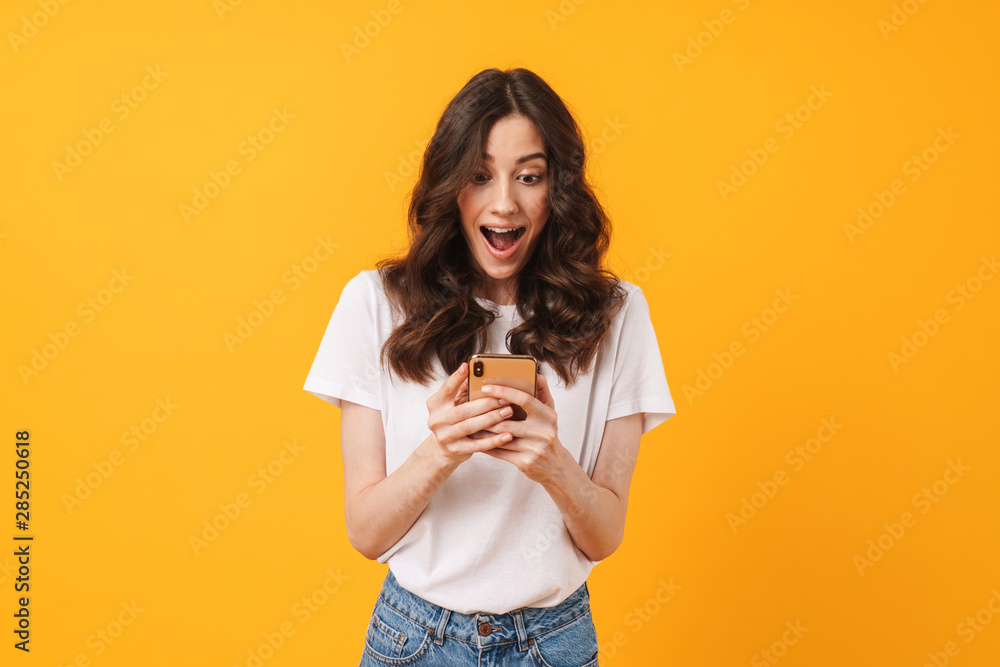 Fototapety, obrazy: Happy shocked emotional young woman posing isolated over yellow wall background using mobile phone.