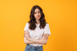 Sad displeased young woman posing isolated over yellow wall background.