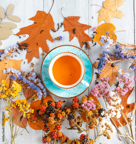 Poster Thee composition still life of a mug with hot leaf tea with berries and autumn leaves on a wooden surface