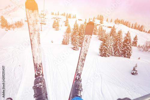 Valokuvatapetti Pair of ski over snow covered forest from skilift