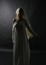 Ghostly Full Length Portrait Of A Woman With Long Blonde Hair Wearing A White Robe. Standing Pose  Against A Black Studio Background.