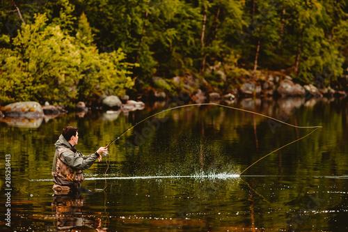 Fotografie, Obraz Fisherman using rod fly fishing in mountain river