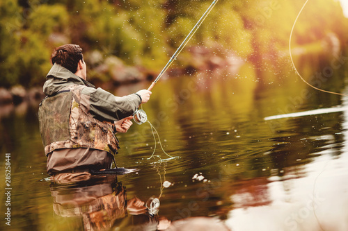 Poster de jardin Peche Fisherman using rod fly fishing in mountain river