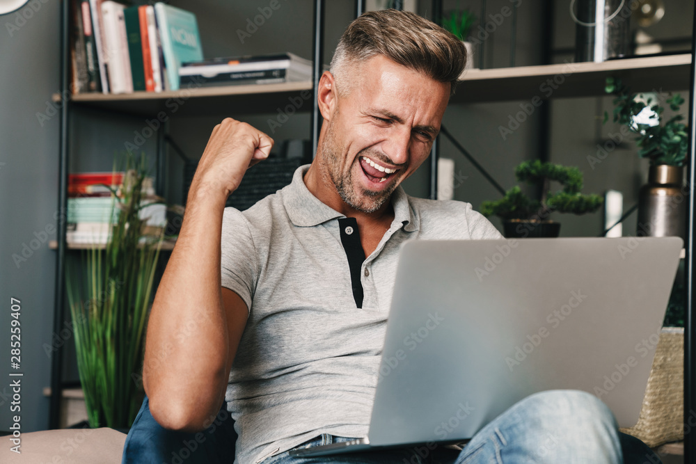 Fototapeta Photo of excited adult man smiling and celebrating while using laptop in apartment