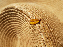 A Yellow Leaf Fallen From A Tree Lies On A Straw Hat. Autumn Concept, Accessories.