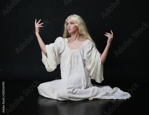 Stampa su Tela Ghostly  portrait of a woman with long blonde hair wearing a white robe