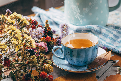 Spoed Foto op Canvas Thee autumn warming tea on a wooden table with autumn tree leaves lying nearby