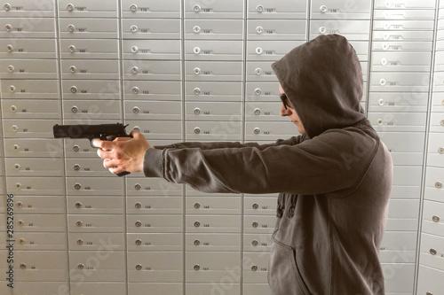Einbrecher mit Waffe vor Schließfächern Canvas Print